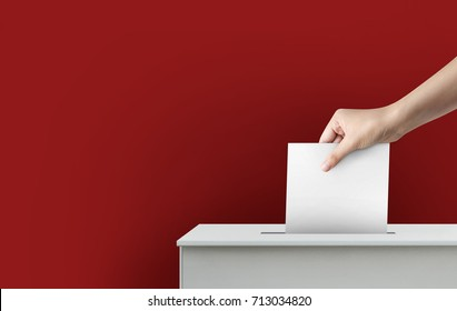 Woman hand holding ballot paper for election vote concept at red background.