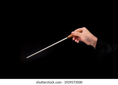 Woman hand holding Baton or Magic wand conjured up in the air. on black background, Miracle magical stick Wizard for fantasy story.