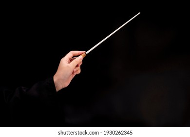Woman hand holding Baton or Magic wand conjured up in the air. on black background, Miracle magical stick Wizard for fantasy story. - Shutterstock ID 1930262345