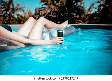 Woman hand holding beer can floating on the blue pool water and relaxing. Copy space