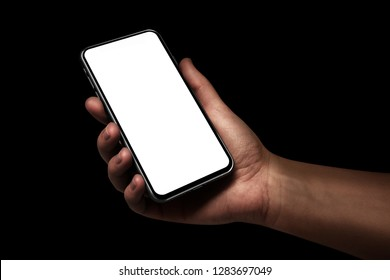 Woman hand holding the black smartphone with blank screen and modern frame less design angled position - isolated on black background