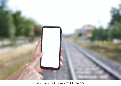 Woman hand holding black smartphone and pointing screen, blank white screen for mockup. Blurry train railway in the background. Journey and travel concept.