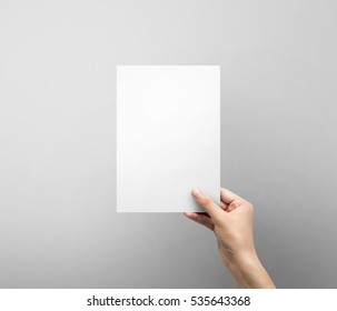 Woman hand holding blank paper sheet A5 size or letter paper on grey background.
