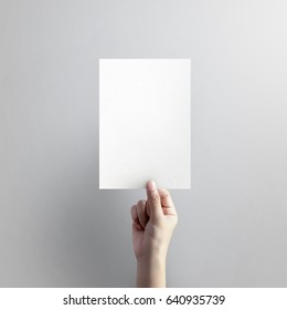 Woman hand holding blank paper sheet A5 size on grey background.