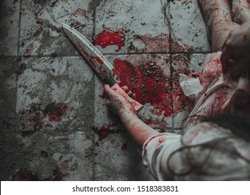 Woman hand holding a bloody knife. Psycho woman self harming with knife. Hand full of blood and wrist cut. Drop and blob of blood on floor. Halloween concept. Suicide concept. Self harm concept.