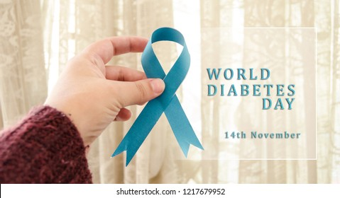 woman hand holding blue ribbon, text world diabetes day concept
