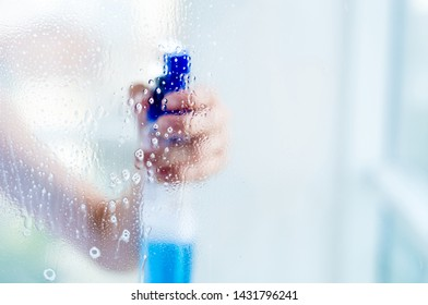 Woman hand holding bottle of blue cleaning spray, through transparent window