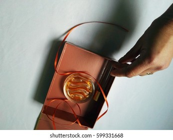 woman hand holding brown open box with perfume