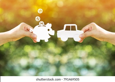 Woman hand holding a car and piggy bank and dollar coin model made of paper art filed together on nature bokeh in the public park, Loan or save money for buy a new chattel concept.
