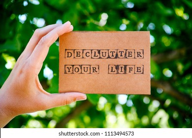 Woman hand holding cardboard card with words Declutter Your Life made by black alphabet stamps against green nature background.