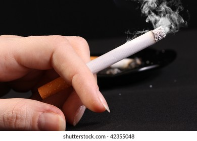 woman hand holding a cigarette with smoke