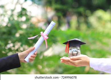 Woman hand holding coins money in glass bottle with graduates hat and diploma on natural green background, Saving money for education concept