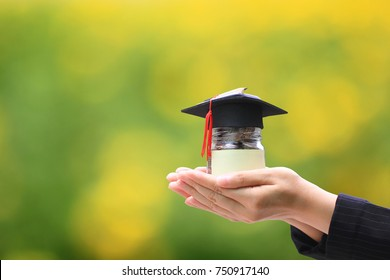 Woman hand holding coins money in glass bottle with graduates hat on natural green background, Saving money for education concept