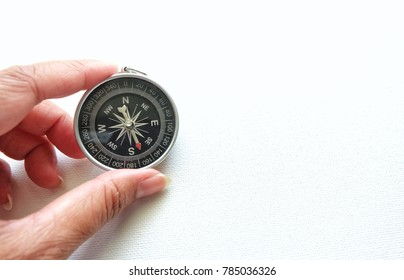 Woman hand holding a compass on white background.