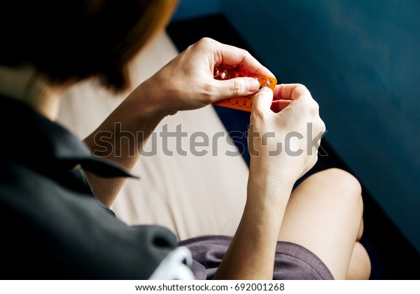 Woman hand holding contraceptive pill ready to eat.