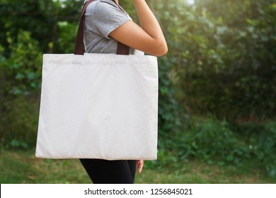 woman hand holding cotton bag on green background. eco concept