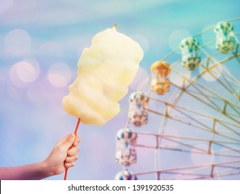 Woman hand holding cotton candy over ferris wheel on blue sky blur background, vintage filter effect.