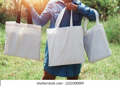 woman of hand holding cotton Tote Bag three on green grass background. concept eco and recycling