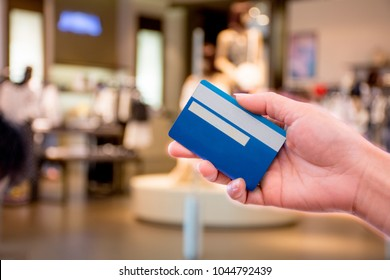 Woman hand holding credit card  for payment shopping in department store, blurred background. e commerce and m banking concept.
