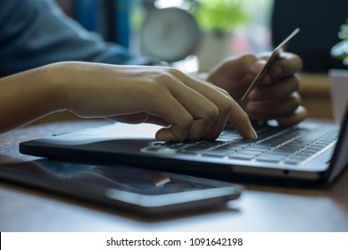 Woman hand holding credit card  and using laptop computer searching application for online shopping  and payment at home office.