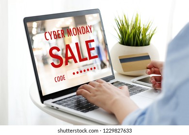 Woman hand holding credit card and tying laptop computer with cyber monday sale on screen device to shopping online, business and technology, digital marketing