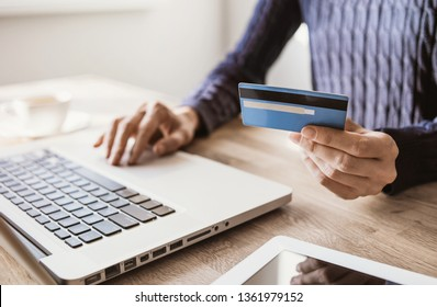 Woman hand holding credit card and using laptop. Businesswoman or entrepreneur working. Online shopping, e-commerce, internet banking, spending money concept