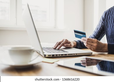 Woman hand holding credit card and using laptop computer. Businesswoman or entrepreneur working. Online shopping, e-commerce, internet banking, spending money concept