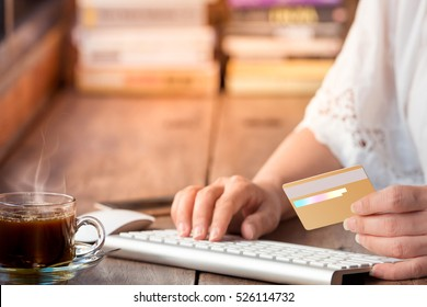 Woman hand holding credit card and using computer keyboard for online payment in coffee shop.Internet banking.