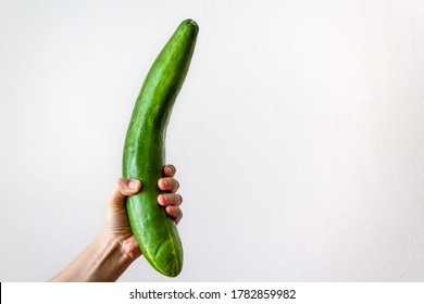 Woman hand holding cucumber on white background