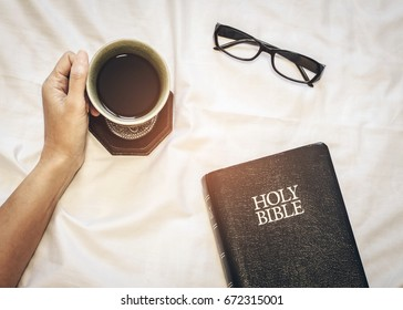 woman hand holding a cup of black coffee  with holy bible and eyeglasses on bed in morning devotion time, christian background