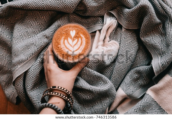Woman hand holding cup of cappuccino coffee with latte art. Warm scarf blanket. View from above.
