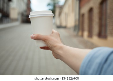 Woman hand holding a cup of coffee, street view