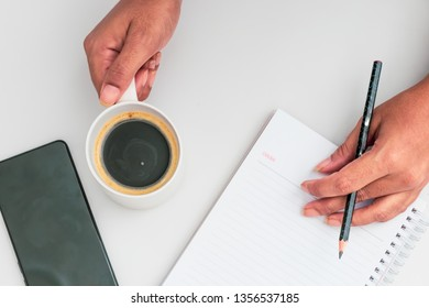 Woman hand holding cup of coffee, open notebook Flat lay
