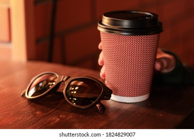 woman hand holding cup of coffee, glasses on the wood table,  brick wall background