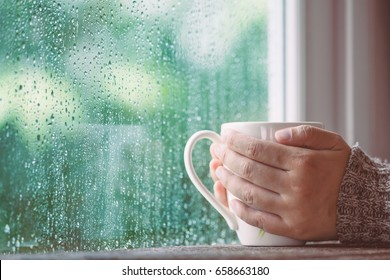 Woman hand holding the cup of coffee or tea on rainy day window background in vintage color tone