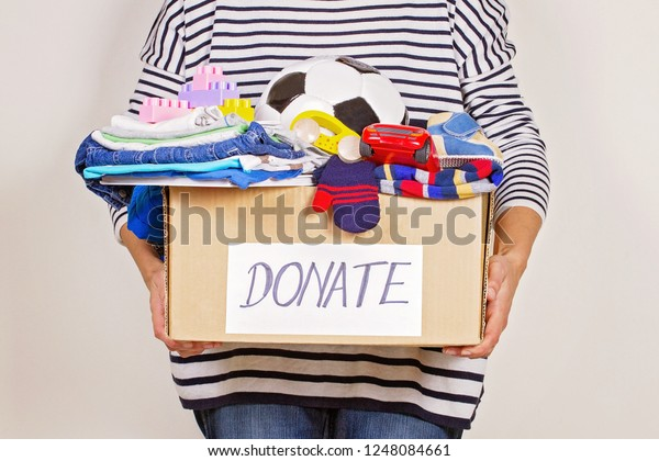 Woman hand holding donation box with clothes, toys and books for charity