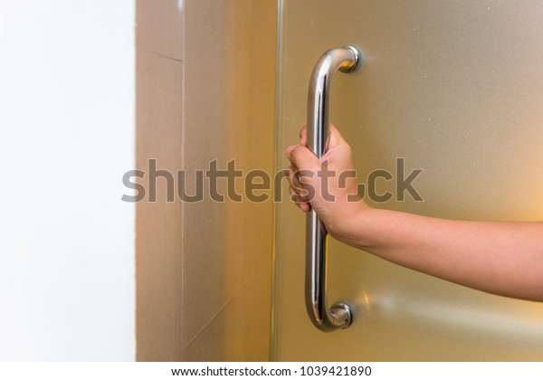 Woman Hand is Holding Door Handle While Opening a Door, Close-Up of Waitress Women Open Door for Customer in Office Building. Interior Decorative Design Private Room for Security Residential.