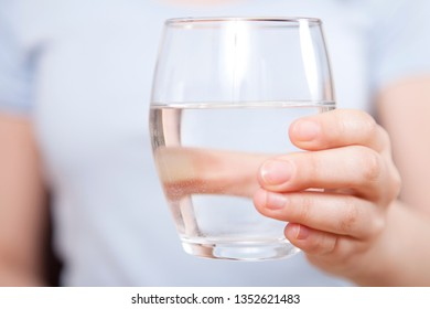 Woman is hand holding drinking water on gray background