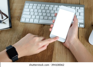 woman hand holding empty screen of smart-phone on wood desk work.
