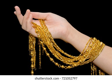 Woman hand holding expensive golden chains on black background