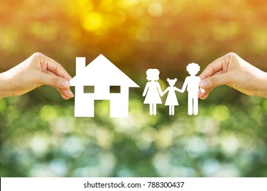 Woman hand holding a family and home model with paper art filed together on nature bokeh in the public park, The saving money for house or real estate owner in the future concept.
