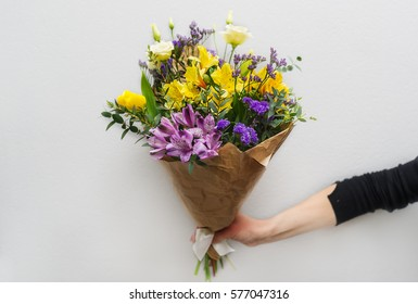 Woman hand holding flowers. Bouquet of flowers for congratulations.