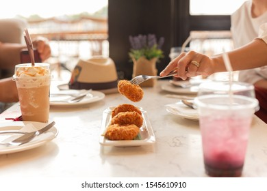 Woman hand holding fork taking food with drink on table.