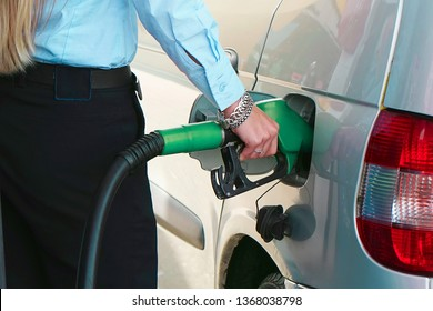 Woman hand holding a fuel pump at a station. Woman fills petrol into her car at a gas station close-up. Toning.