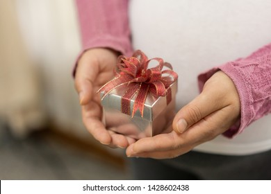 Woman hand holding a gift box of christmas present.