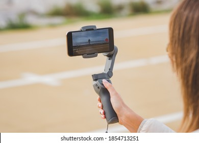 Woman hand holding gimbal with phone. Taking pictures and live video near the ocean. Vlog and video blogging concept.