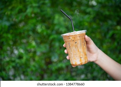 Woman hand holding the glass iced coffee on green nature background