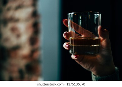 Woman hand holding glass of whisky. Close up shot of alcoholic drink