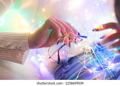 Woman hand holding glasses and christmas lights
