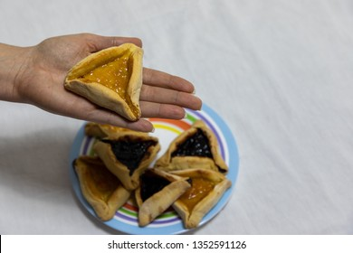 Woman hand holding hamantash cookie on top of colorful plate with more hamantash cookies